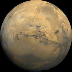 Der Mars. In der Bildmitte erkennt man das größte Canyonsystem des Sonnensystems, Valles Marineris. Die dunklen Flecken links sind die Vulkane Ascraeus Mons, Pavonis Mons und Arsia Mons. Vulkanische Aktivität könnte in der Frühzeit des Planeten genug Methan freigesetzt haben, um wärmere Bedingungen zu schaffen, die flüssiges Wasser auf der Oberfläche ermöglichten. (Jody Swann / Tammy Becker / Alfred McEwen / USGS / NASA)