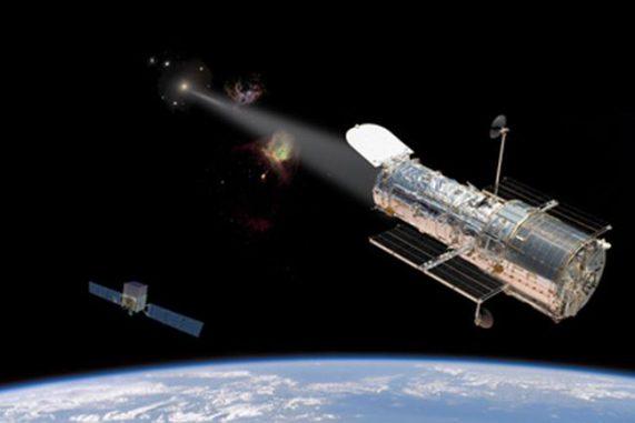 Illustration des Hubble Space Telescope bei der Beobachtung ultravioletter Strahlung, die von dem Teilchenjet des aktiven galaktischen Kerns in PKS 1424+240 emittiert wird. Der Satellit unten links stellt das Fermi Gamma-ray Space Telescope dar. (Image composition by Nina McCurdy, component images courtesy of NASA)