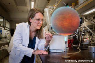 Dieses Bild zeigt Heather Knutson in einem Labor am California Institute of Technology in Pasadena. Ein computergeneriertes Bild eines heißen Jupiters wurde digital in das Bild eingefügt. Tatsächlich arbeitet Knutson nicht im Labor und trägt weder Laborkittel noch Schutzbrille, sondern durchforstet Teleskopdaten auf ihrem Computer im Büro. (NASA / JPL-Caltech)