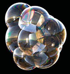 Eine Ansammlung von Seifenblasen mit Wechselwirkungen, die Regenbogenfarbtöne hervorbringen, ähnlich wie ein Ölfleck auf Asphalt. Die Blasen reflektieren einen Strand bei Sonnenuntergang. (UC Berkeley)