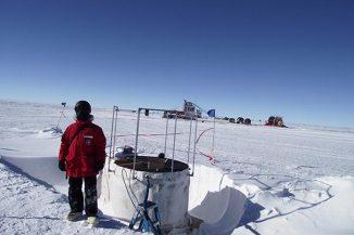 Der Physiker Bakhtiyar Ruzybayev von der University of Delaware neben einem IceTop-Detektor für kosmische Strahlen am Südpol. (University of Delaware)