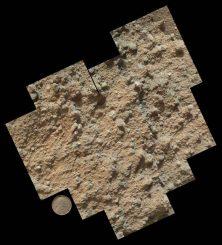 Ein Mosaik aus neun Einzelbildern des Mars Hand Lens Imager an Bord des Marsrovers Curiosity. Es zeigt die detaillierte Oberflächenbeschaffenheit eines Konglomeratgesteins, das aus kleinen Kieseln und sandkorngroßen Partikeln besteht. Als Größenvergleich dient der Lincoln-Penny des Instruments. (NASA / JPL-Caltech / MSSS)