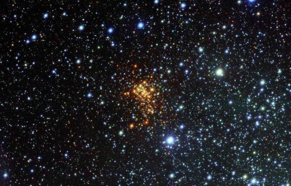 Das neue VST-Bild des Sternhaufens Westerlund 1. Die Sterne in dem Sternhaufen erscheinen rot aufgrund von Staub, der ihr blaues Licht blockiert. Die blauen Sterne sind Vordergrundobjekte und gehören nicht zu dem Sternhaufen. Der Stern W26 befindet sich oben links in dem Sternhaufen und ist von einem grünen Leuchten umgeben. (ESO / VPHAS+ Survey / N. Wright)