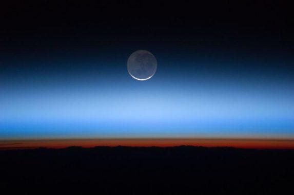 Auf diesem Foto befindet sich die Sonne kurz unterhalb des Horizonts und erzeugt ein orange-rotes Leuchten über der Oberfläche in der Troposphäre. Die Tropopause ist die braune Linie am oberen Rand der Troposphäre. Darüber liegen die Stratosphäre, höhere Atmosphärenschichten und die Schwärze des Weltalls. (NASA / Johnson Space Center)