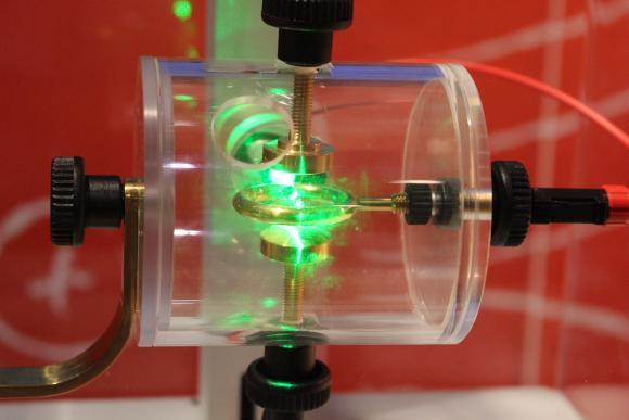 Ein Ionenkäfig nach dem Vorbild Wolfgang Pauls. Elektrisch geladene Bärlappsporen sind in wechselnden elektrischen Feldern gefangen und werden von einem Laser erleuchtet. (astropage.eu mit freundlicher Genehmigung des Deutschen Museums Bonn)