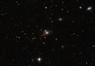 Der Zwillingsquasar QSO 0957+561 leuchtet hell in der Bildmitte. Das Doppelbild entsteht durch eine sogenannte Gravitationslinse, bei der ein näher liegendes Objekt (hier eine Galaxie und ein Galaxienhaufen) das Licht eines entfernten Objekts (hier der Quasar) beugt. (ESA / Hubble & NASA)