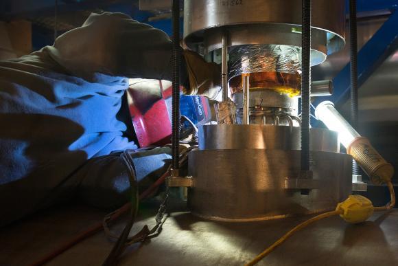 Ein Schweißer arbeitet an der ersten supraleitenden Radiofrequenzkammer am RHIC. (Courtesy Brookhaven National Laboratory)