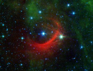 Der rote Bogen auf diesem Infrarotbild des Spitzer Space Telescope ist eine gigantische Schockwelle, die von einem schnellen Stern namens Kappa Cassiopeiae erzeugt wird. (NASA / JPL-Caltech)