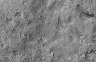 Diese Aufnahme machte die HiRISE-Kamera an Bord des Mars Reconnaissance Orbiter am 27. Juni 2014. Sie zeigt den Marsrover Curiosity an der Grenze der Landeellipse (blaue Linie). (NASA / JPL-Caltech / Univ. of Arizona)