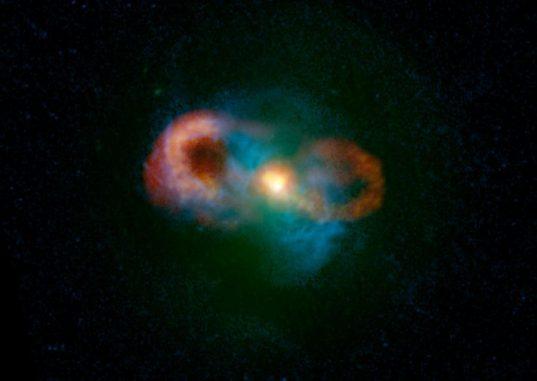 Kompositbild der Teacup-Galaxie. Grüne Farben zeigen Sternlicht, blaue zeigen das Gas und rote/gelbe Farben kennzeichnen die Radioemissionen. Die hellen Bereiche in der Bildmitte zeigen, wo die Jets von dem Schwarzen Loch erzeugt werden und auf das umgebende Gas treffen. (C. Harrison, A. Thomson; Bill Saxton, NRAO / AUI / NSF; NASA)