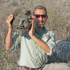 Dr. Michael Eisenberg mit der neu entdeckten Bronzemaske. (Image courtesy of University of Haifa)