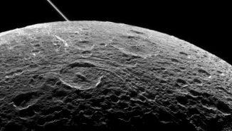 Der Saturnmond Dione während eines Vorbeiflugs der Raumsonde Cassini am 16. Juni 2015. Die diagonale Linie oben links sind die Saturnringe, aufgenommen aus einiger Entfernung. (NASA / JPL-Caltech / Space Science Institute)