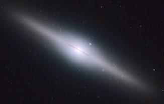 Das Bild zeigt die 300 Millionen Lichtjahre entfernte Galaxie ESO 243-49. Der rote Pfeil kennzeichnet die Position des neu entdeckten mittelschweren Schwarzen Lochs. (NASA, ESA and S. Farrell (U. Sydney))