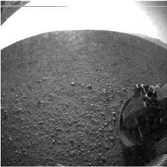 """Dies ist eines der ersten Bilder, die der Mars-Rover Curiosity zurückgeschickt hat. Es wurde mit einer Fischaugen-Linse im linken """"Auge"""" einer Stereo-Kamera gemacht. Der helle Bogen ist ein Sättigungseffekt durch die Helligkeit der Sonne. (NASA / JPL-Caltech)"""