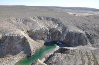 Luftbild des Gebietes. Neben dem Fluss George sind steil abfallende Sedimentschichten erkennbar. Diese deformierten Gesteinsbetten repräsentieren die zentrale Erhebung, die durch die Rückfederung des Gesteins nach dem Einschlag entsteht. (Photo by Brian Pratt)