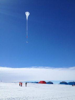 Ein weißer Ballon der BARREL-Mission schwebt in den antarktischen Himmel. Die Gebäude im Hintergrund gehören zur neuen Forschungsstation Halley VI, die in der Wintersaison 2012/2013 erstmals voll einsatzfähig ist. (NASA / R. Millan)