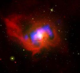 Kompositbild der Zentralregion von NGC 4696, basierend auf Daten von Chandra (rot), dem VLA (blau) und Hubble (grün). (Credits: X-ray: NASA / CXC / MPE / J.Sanders et al.; Optical: NASA / STScI; Radio: NSF / NRAO / VLA)