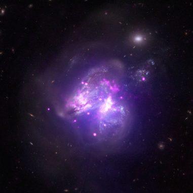 Arp 299 auf Basis von Daten der Weltraumteleskope Chandra, NuSTAR und Hubble. (Credit: X-ray: NASA / CXC / Univ of Crete / K. Anastasopoulou et al, NASA / NuSTAR / GSFC/A. Ptak et al; Optical: NASA / STScI)