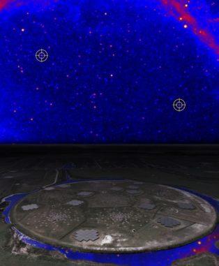 """Künstlerische Darstellung des LOFAR """"Superterp"""" bei Exloo (Niederlande), darüber ein Teil des von Fermi beobachteten Himmels im Gammabereich. Die Positionen der Pulsare J0952-0607 (Mitte rechts) und J1552+5437 (oben links) sind markiert. (Credits: NASA / DOE / Fermi LAT Collaboration and ASTRON)"""