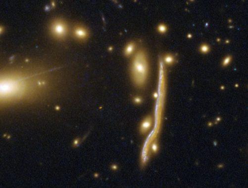 Die Kosmische Schlange, eine durch den Gravitationslinseneffekt verzerrte Galaxie. (Credits: ESA / Hubble, NASA)