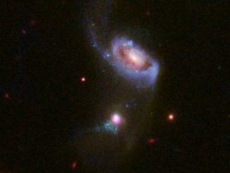 Hubble-Aufnahme der Galaxie SDSS J1354+1327 (unten) mit zwei abgestoßenen Gasblasen. (Credits: NASA, ESA, and J. Comerford (University of Colorado-Boulder))