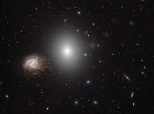 Die beiden Galaxien NGC 4680 (Mitte) und NGC 4858 (links), aufgenommen vom Weltraumteleskop Hubble. (Credits: ESA / Hubble & NASA)
