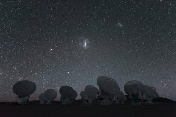 Die beiden Magellanschen Wolken am Nachthimmel über der Südhalbkugel, im Vordergrund die Antennen des Atacama Large Millimeter/ submillimeter Array (ALMA). (Credits: ESO / C. Malin)