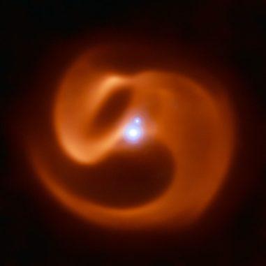 Dieses Bild basiert auf Daten des Very Large Telescope der Europäischen Südsternwarte in Chile. Es zeigt das neue System mit den beiden Sternen mit dem massereicheren im Zentrum und dem Begleiter ein Stück nordwestlich. Das massereichere Objekt selbst ist ebenfalls ein Doppelsternsystem, das hier nicht aufgelöst werden kann. Die Staubstruktur des Systems ist in rötlichen Farben dargestellt. (Credit: Photo Credit: University of Sydney / European Southern Observatory)