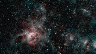 Der Tarantelnebel, aufgenommen vom Weltraumteleskop Spitzer in infraroten Wellenlängen. Die roten Regionen weisen auf die Präsenz von besonders heißem Gas hin, während die blauen Regionen interstellaren Staub kennzeichnen. (Credits: NASA / JPL-Caltech)
