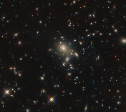 Die dem Gravitationslinseneffekt unterliegende Galaxie PLCK G045.1+61.1 ist in Form mehrerer rötlicher Punkte nahe der Bildmitte erkennbar. (Credit: ESA / Hubble & NASA, B. Frye)
