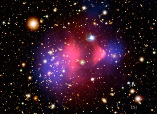 Kompositbild eines Galaxienhaufens, der aus der Kollision zweier großer Galaxienhaufen hervorging. Heißes röntgenemittierendes Gas ist pink dargestellt, Dunkle Materie (abgeleitet anhand ihrer Gravitation) in Blau. (Credits: X-ray: NASA / CXC / CfA / M.Markevitch et al.; Optical: NASA / STScI; Magellan / U.Arizona / D.Clowe et al.; Lensing Map: NASA / STScI; ESO WFI; Magellan / U.Arizona / D.Clowe et al.)